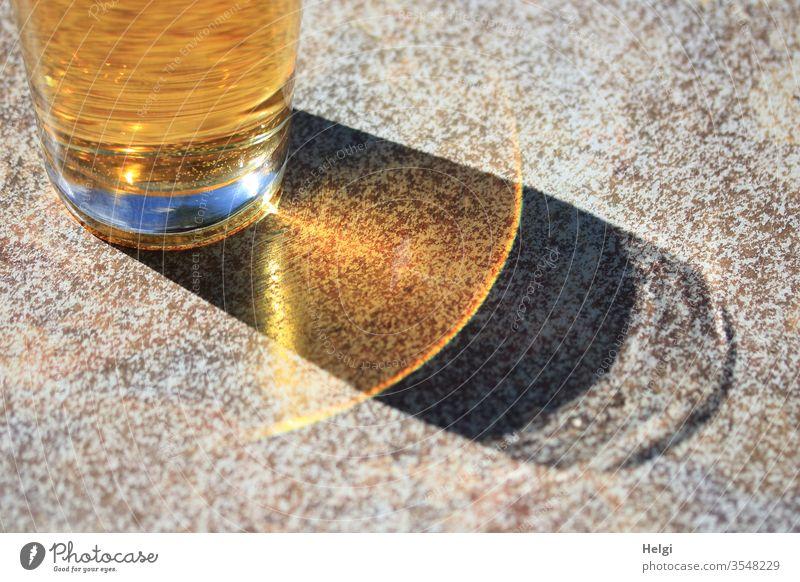 Erfrischungsgetränk im Sonnenschein mit Schatten und Reflexion Getränk Glas Apfelschorle Tisch Licht Sonnenlicht leuchten außergewöhnlich Detailaufnahme gelb