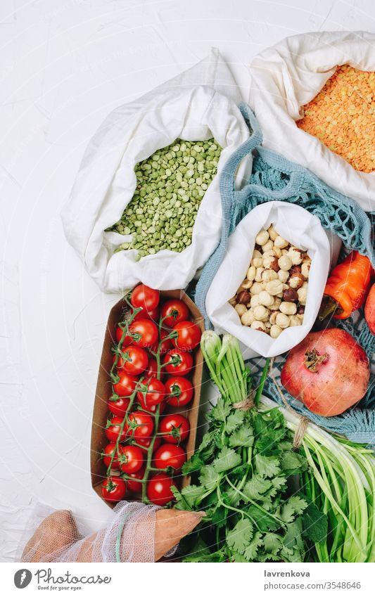 Konzept des abfallfreien, nachhaltigen Lebensmitteleinkaufs: Tomaten, Erbsen, verschiedene Grünsorten, Haselnüsse usw. in Produktbeuteln batata Bohnen Chili