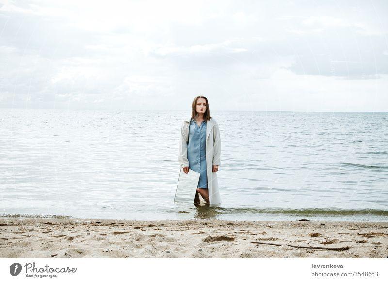 Nahaufnahme einer am Ufer stehenden Frau in blauem Kleid, die einen Spiegel mit reflektierendem Wasser in der Hand hält, selektiv Erwachsener Strand Kaukasier