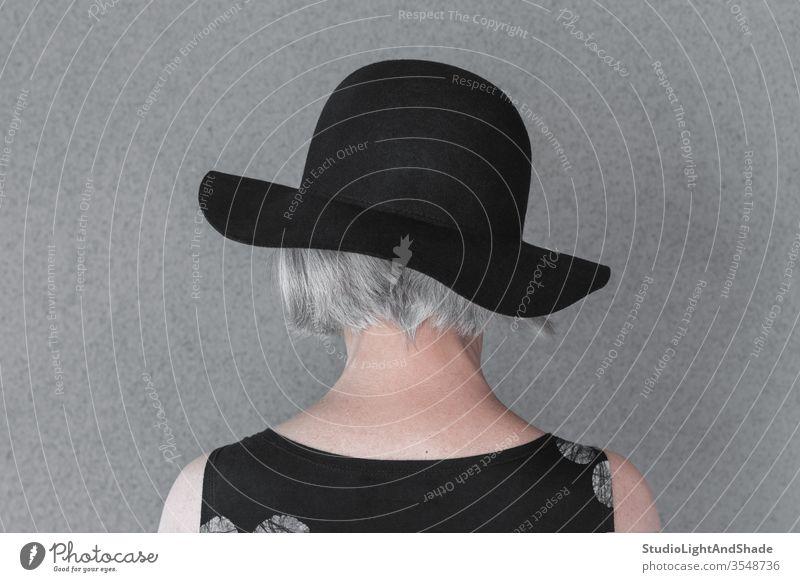 Grauhaarige Dame mit schwarzem Hut Kopf Hals grau Behaarung grauhaarig Person Frau 50s 60s Rücken Mode modisch Kleid elegant Stil stylisch Senior Lebensalter