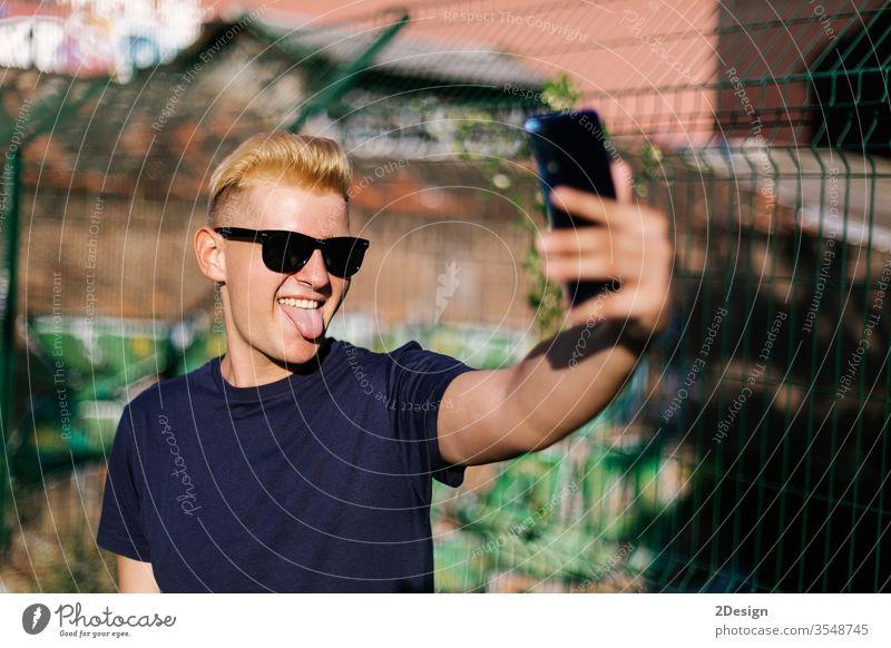 Junger Teenager mit Sonnenbrille bei einem Selbstversuch im Freien männlich jung Selfie Telefon 1 Mann Person benutzend Porträt Smartphone modern Beteiligung