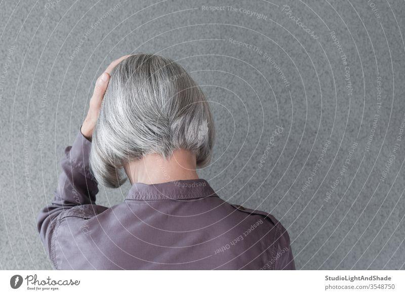 Verärgerte grauhaarige Frau Kopf Behaarung purpur Silber Haarschnitt Frisur Person verärgert traurig Trauer trauern unglücklich Traurigkeit Verzweiflung