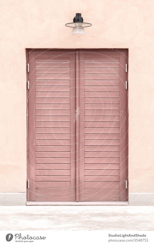 Rosa Gebäude mit einer Holztür Tür Eingang rosa rot Pastell zugeklappt hölzern Haus heimwärts Lampe Straßenlaterne Außenseite Großstadt Stadt urban Europa