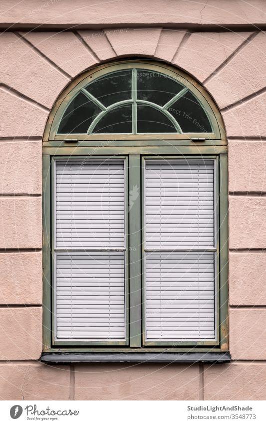Rosa Gebäude mit abgerundetem grünen Fenster Rahmen rosa staubig-rosa Pastell Haus Wand Privatsphäre privat zugeklappt Jalousien Gardine Schatten Europa