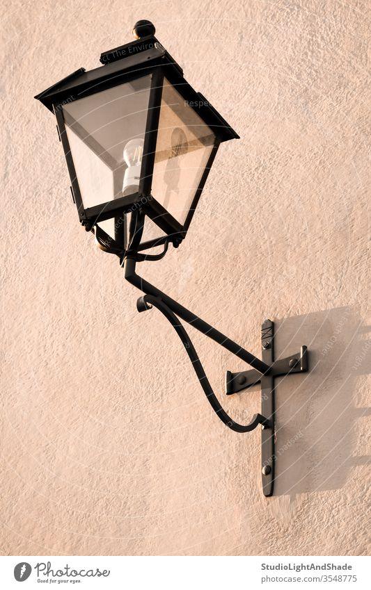 Vintage Straßenlaterne auf einer rosa Wand Licht Lampe Laterne staubig-rosa Pastell schwarz Elektrizität gemalt Stein Hintergrund Textur Oberfläche Metall