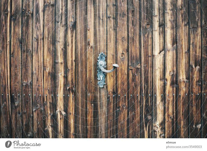 gusseiserne Türblende (Türklinke) im Vintagestil an dunkelbraunem Holztor Sicherheit Metall Privatsphäre Maserung verschlossen Beschränkung abgeschlossen
