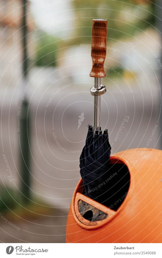 Schwarzer Regenschirm mit Holzgriff steckt in orangefarbener Mülltonne schwarz Griff stecken Sonne Schwache Tiefenschärfe oval Berlin BSR Straße Abfall