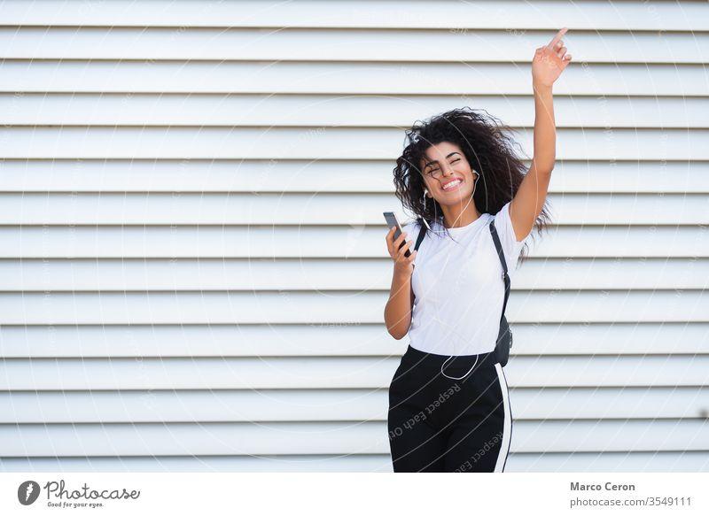 schönes gemischtrassiges Mädchen, das auf der Straße fröhlich Musik hört Dreiviertellänge jung weißer Hintergrund gemischte Rasse Tanzen sonnig Frau Lifestyle