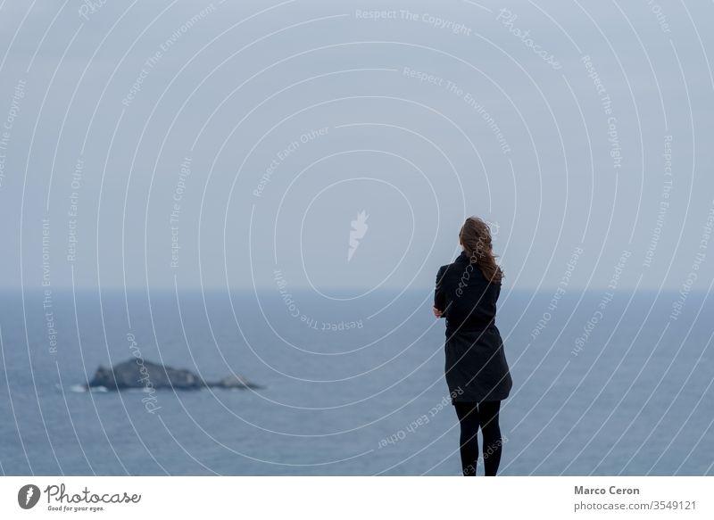 junge Frau, die vor blauem Himmel und Meer steht nachdenklich Denken MEER Horizont kalt Zukunft ätherisch unsicher Traurigkeit Brise ruhige Umgebung im Freien
