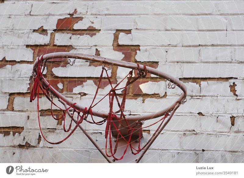 Basketball, alt, schief und rot Basketballkorb Wand Netz Fassade Farbe Backstein Backsteinwand Backsteinfassade Abendlicht menschenleer Mauer Außenaufnahme