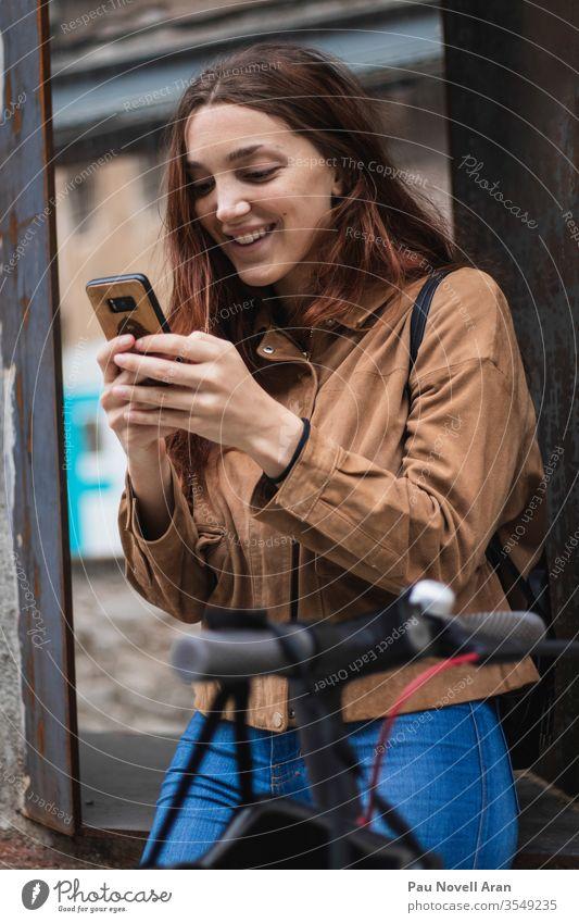 Junge Frau betrachtet Smartphone auf der Straße Stadtleben Lifestyle urban schön Mitteilung Anschluss Gerät Europa Außenseite Apparatur Internet Model Holz