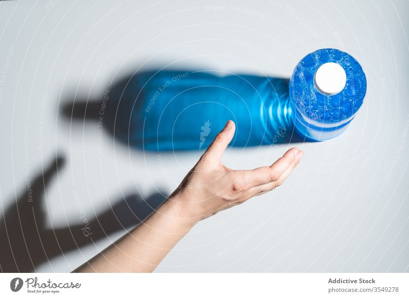 Nicht erkennbare Person, die Hand für Flasche Glitzerwasser zieht Wasser Schatten funkeln durchsichtig Kunststoff natürlich sich[Akk] melden rein Klebeband satt