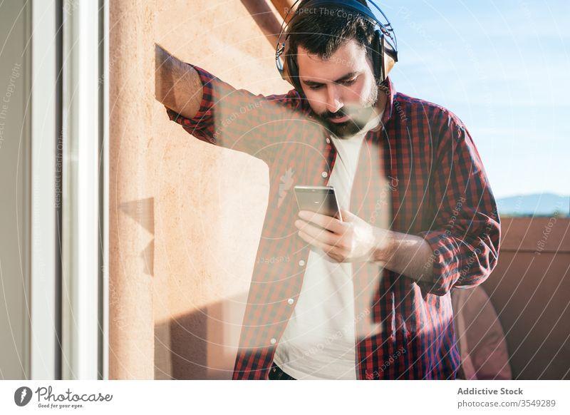 Junger Mann hört zu Hause Musik Smartphone jung Lifestyle außerhalb Typ Telefon Technik & Technologie Mobile Kopfhörer im Freien männlich Funktelefon