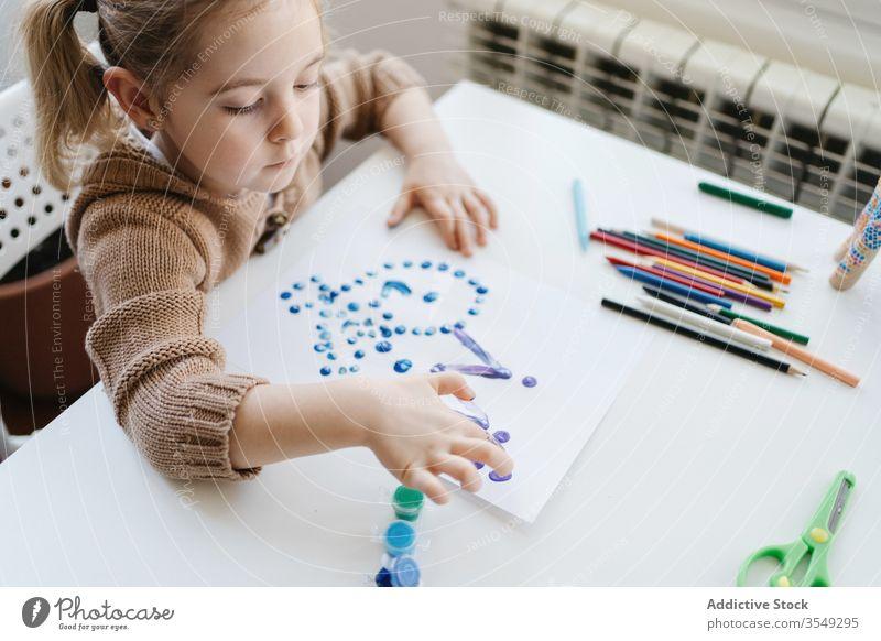 Von oben ein kleines Mädchen, das zu Hause Gouache zum Zeichnen mit den Fingern auf Papier benutzt Zeichnung heimwärts Kind Farbe Kindergarten Kunst kreativ