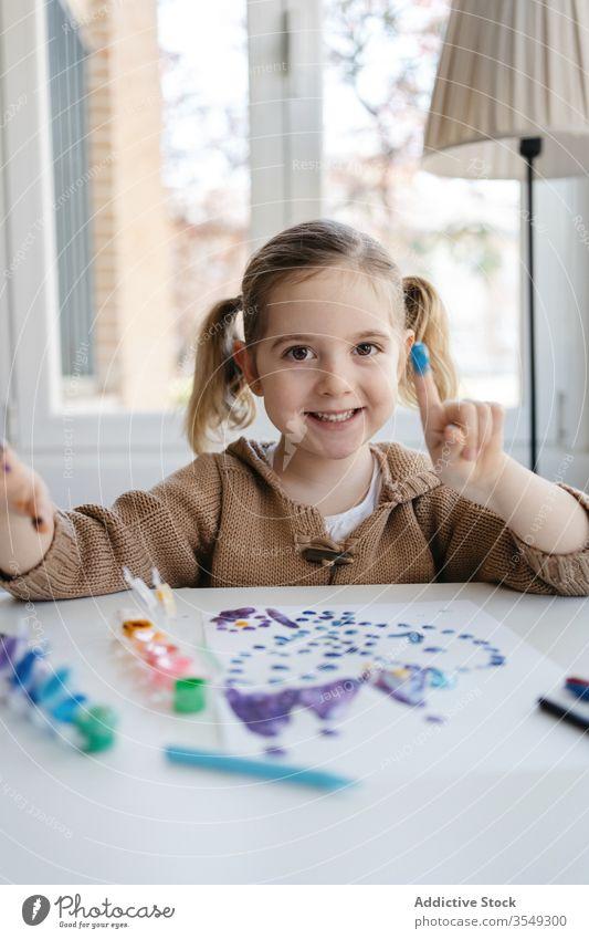 Kleines Mädchen zeigt Finger mit Gouache beim Zeichnen im Wohnzimmer Farbe Papier zeigen zeichnen Punkt spielerisch niedlich Vorschule Zeichnung abstrakt Bild