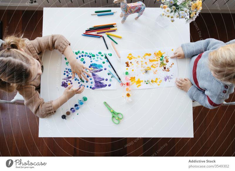 Bruder und Schwester im Vorschulalter malen gemeinsam zu Hause Kinder heimwärts zeichnen Farbe kreativ spielen Vorschule Atelier Wohnzimmer Gouache farbenfroh