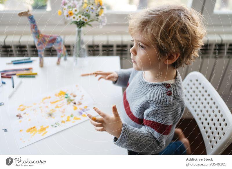 Fokussiertes blondes Kind benutzt Gouache zum Fingermalen zu Hause Junge Farbe zeichnen kreativ heimwärts Kindergarten kleben Zeichnung Papier wenig niedlich