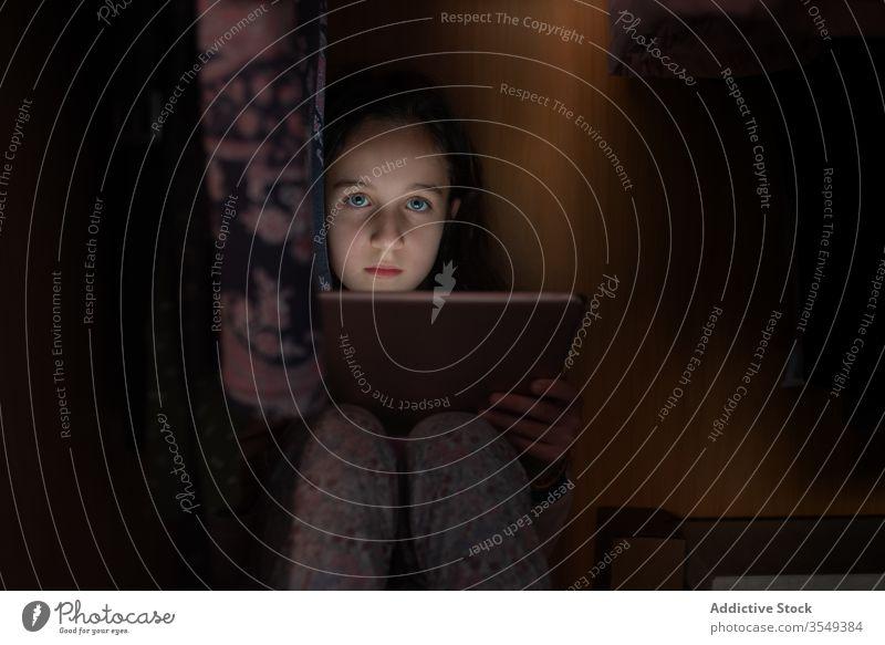 Ernsthaftes kleines Mädchen beobachtet Tablette in dunklem Raum dunkel Kind Nachtwäsche Tierhaut heimwärts ernst sitzen benutzend zuschauen Internet Gerät