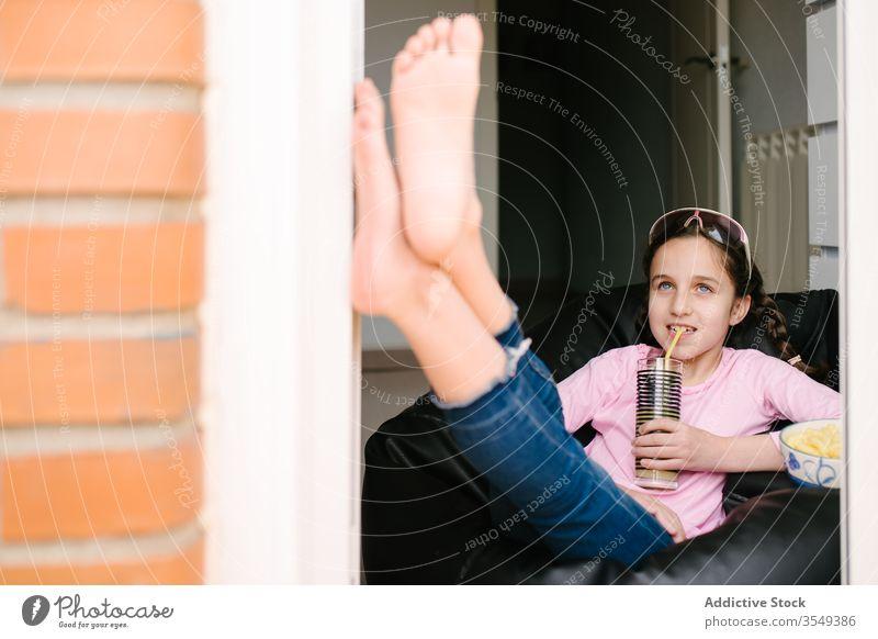 Fröhliches Mädchen trinkt frisches Getränk und ruht zu Hause auf Stuhl räkeln Saft Snack heimwärts Chip Erfrischung Glas Glück Inhalt Sommer Sonnenbrille Teller
