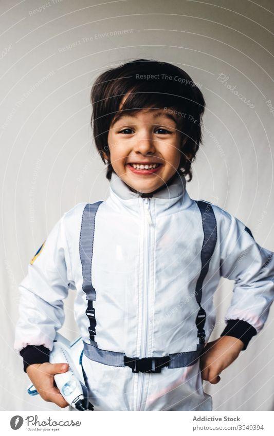 Bezaubernder ethnischer Junge im Kosmonautenkostüm auf weißem Hintergrund Tracht bezaubernd Raumfahrer Spielzeug Raumschiff positiv Kind Astronaut Spaß haben
