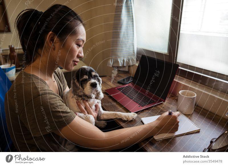 Vielbeschäftigte asiatische Unternehmerin arbeitet im Home Office zu Hause Arbeit Schreibstift Papier Notebook schreibend Frau Projekt Notizblock multitask