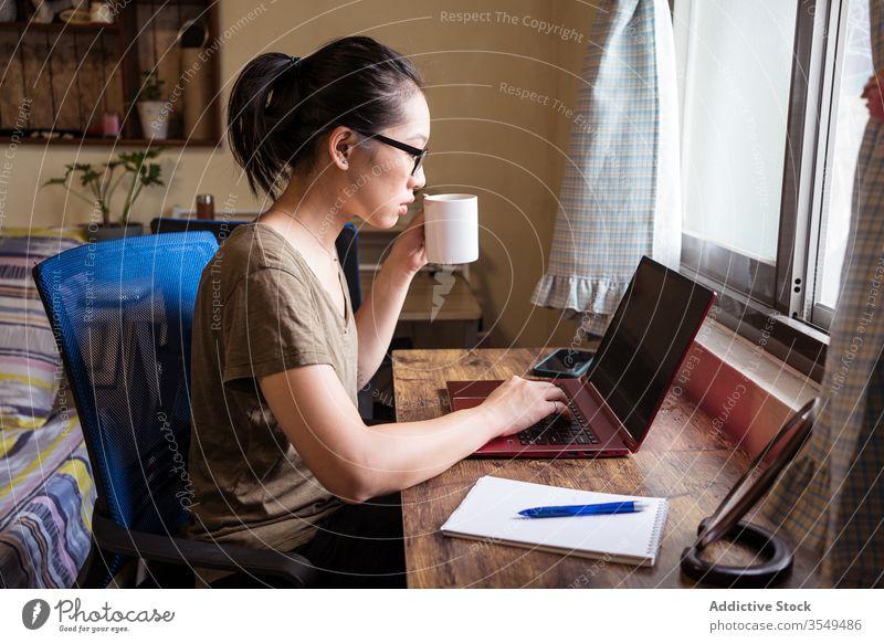 Vielbeschäftigte Unternehmerin tippt am Laptop und trinkt Kaffee Tippen Frau trinken heimwärts Büro benutzend asiatisch ethnisch freiberuflich Konzentration