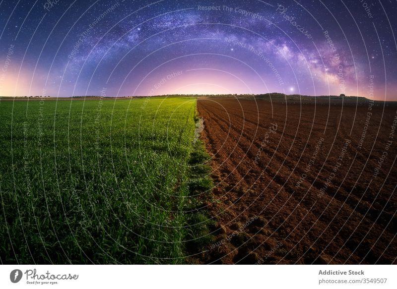 Landwirtschaftliches grünes und gepflügtes Feld Ackerbau Hälfte Nacht Milchstrasse Pflanze Boden Dämmerung Landschaft ländlich Galaxie sternenklar Bauernhof