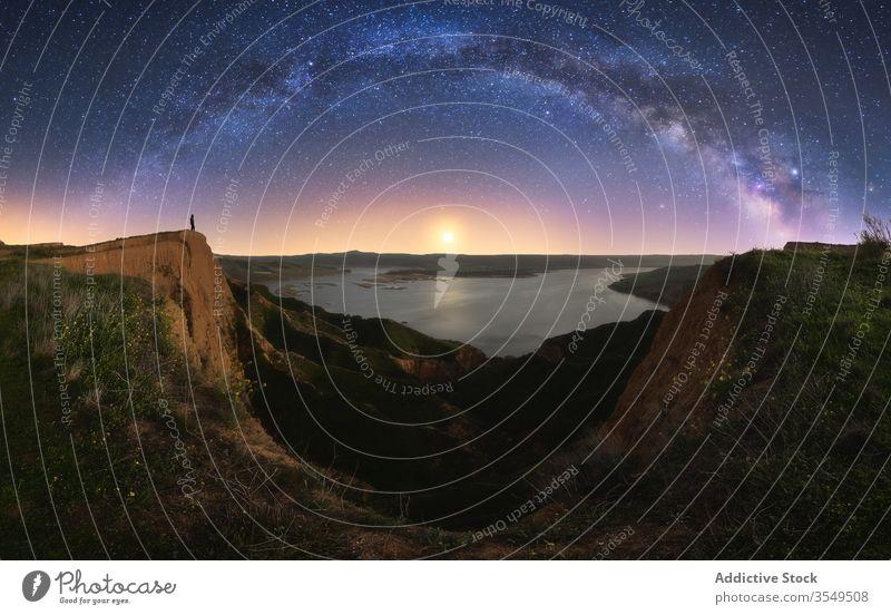 Canyon mit anonymer Person unter farbenfrohem Nachthimmel mit Milchstraße Schlucht Natur See Himmel Milchstrasse Galaxie wolkig Silhouette Wasser Formation