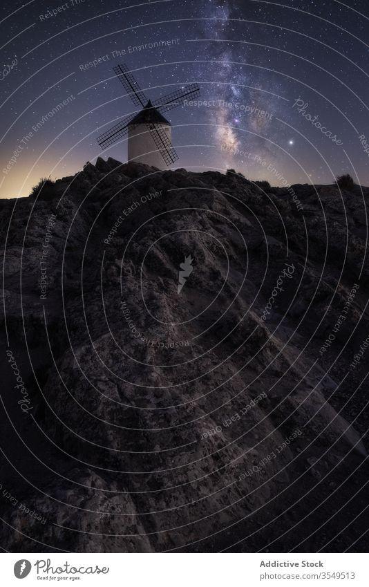 Steiniger Hügel mit holländischer Windmühle in sternenklarer Nacht Landschaft Milchstrasse Berge u. Gebirge Felsen Himmel holländische Windmühle spektakulär