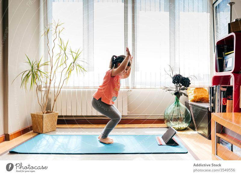 Fröhliches kleines Mädchen macht Yoga im hellen Raum Kind Pose Unterlage Video Tablette Tutorial Gleichgewicht üben zu Hause Stressabbau zuschauen Harmonie