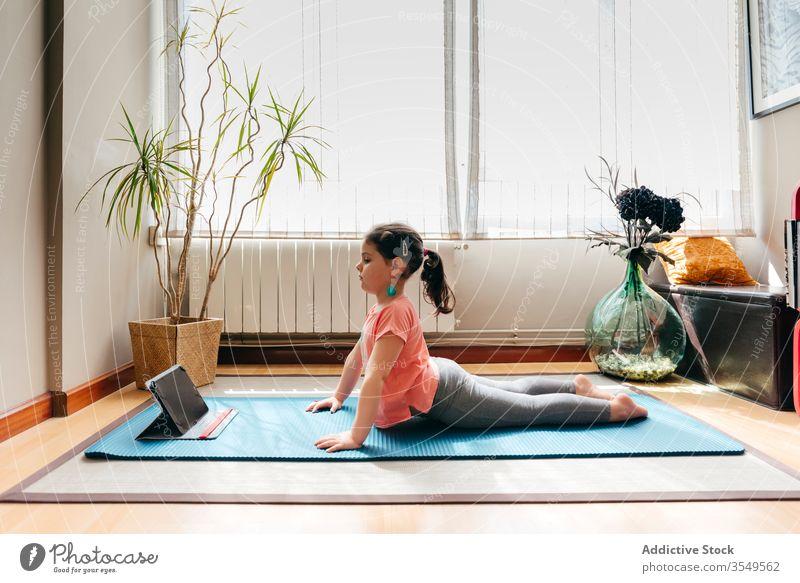 Kleines Mädchen, das Yoga in Kobra-Pose praktiziert Kind Asana üben heimwärts Tablette bhujangasana online beweglich Dehnung wenig Unterlage Gleichgewicht
