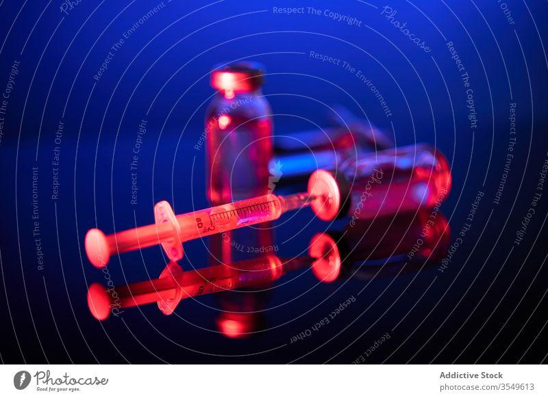 Spritze mit Nadel im dunklen Raum in der Kappe der Flasche Impfstoff Medikament Kur Bund 19 Infektion Virus Coronavirus neonfarbig leuchten durchsichtig
