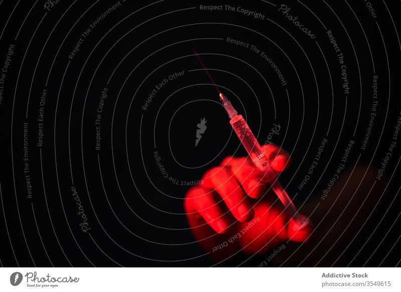 Erntehelfer hält Spritze mit Medikament in rotem Licht auf schwarzem Hintergrund Person Impfstoff Kur Einspritzung Krankenhaus Klinik Bund 19 Coronavirus