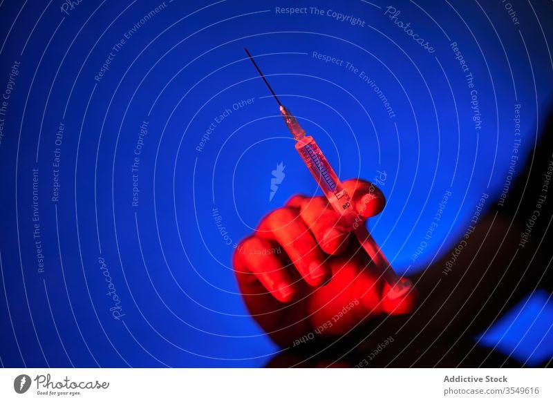Erntehelfer hält Spritze mit Medikament in rotem Licht auf blauem Hintergrund Person Impfstoff Kur Einspritzung Krankenhaus Klinik Bund 19 Coronavirus Infektion