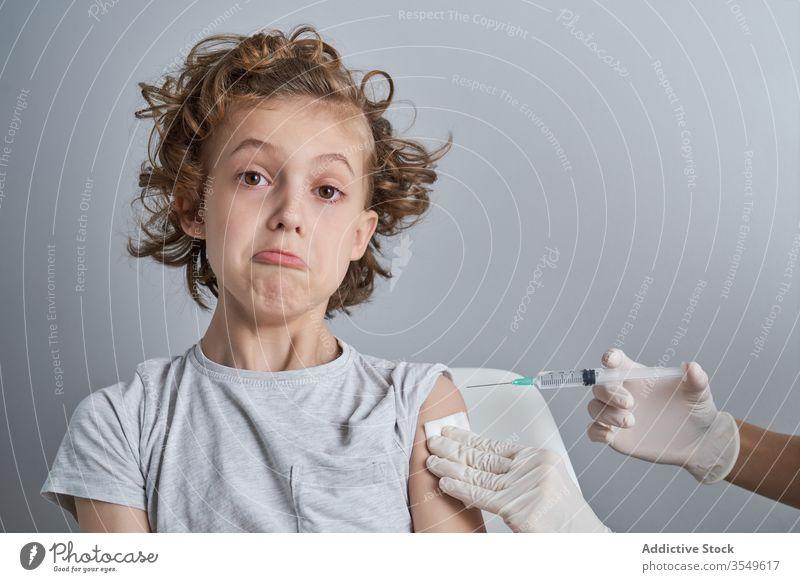 Anonymer Arzt hält Jungen während der Injektion in der Klinik an der Schulter Impfstoff Einspritzung Leckerbissen Spritze Medizin Handschuh geduldig