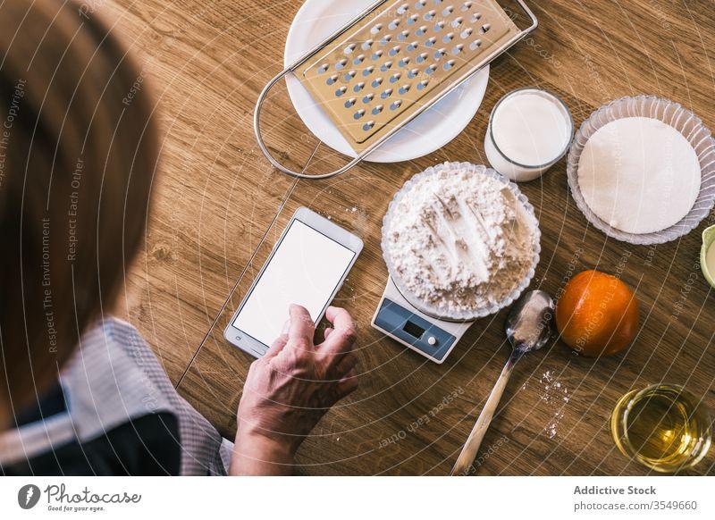 Frau benutzt Mobiltelefon während der Zubereitung von Gebäck Bestandteil backen Smartphone Skala Browsen Gewicht Teigwaren Küche vorbereiten Koch Hand Rezept