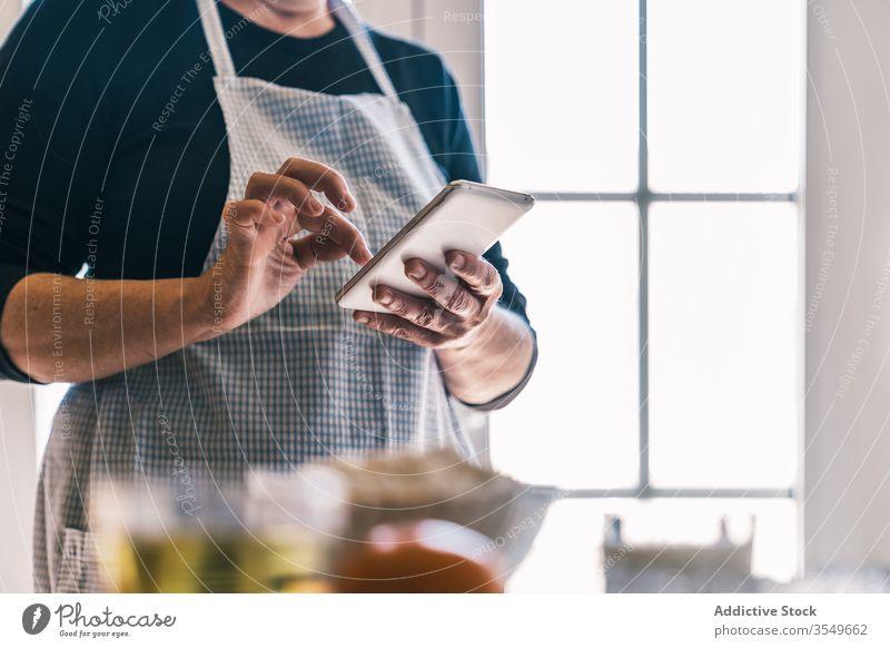 Anonyme Frau benutzt Smartphone in der Küche Rezept Hausfrau benutzend heimwärts Browsen Internet prüfen reif Senior Schürze Lächeln Kommunizieren positiv Koch