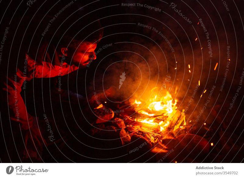 Mann mit Brennholz beim Lagerfeuermachen im Wald Wohnmobil Freudenfeuer Nacht Totholz Aufwärmen männlich Windstille Reisender ruhig Wälder genießen Wochenende