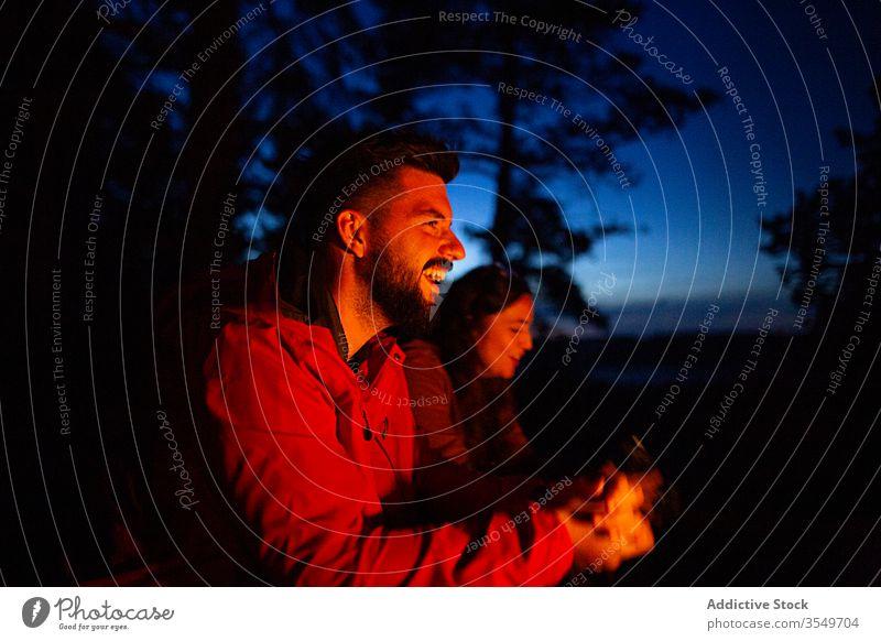 Paar mit Brennholz beim Lagerfeuermachen im Wald Wohnmobil Freudenfeuer Nacht Totholz Aufwärmen Freunde Reisender Wälder genießen Abend Frau Zusammensein Mann