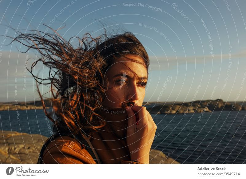 Nachdenkliche junge Touristin steht am felsigen Meeresufer und schaut weg Frau Reisender Harmonie träumen besinnlich wellenförmiges Haar Wind Natur Küste reisen