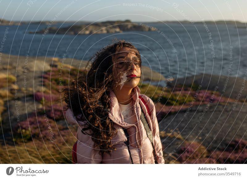 Junge Frau am Seeufer stehend Brise genießen sonnig Windstille ruhig Gelassenheit gewelltes Haar sich[Akk] entspannen Urlaub Feiertag ruhen Wasser Fluss