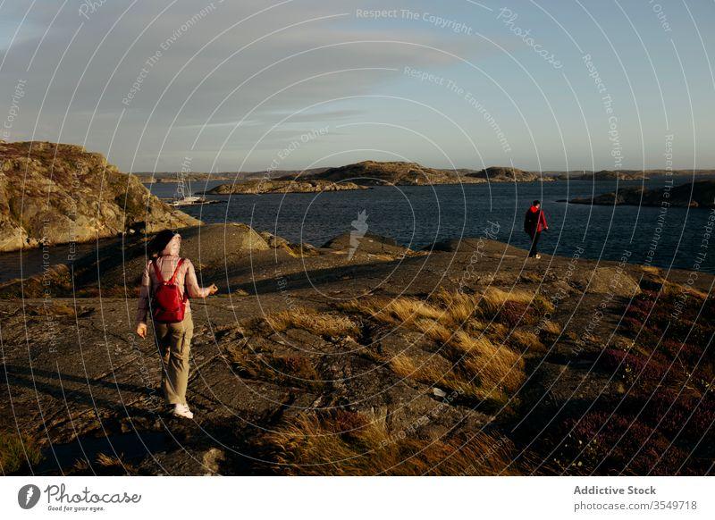 Anonymes Touristenpaar geht am felsigen Meeresufer spazieren Paar Zusammensein Meereslandschaft Oberbekleidung Urlaub Natur reisen Abenteuer Tourismus