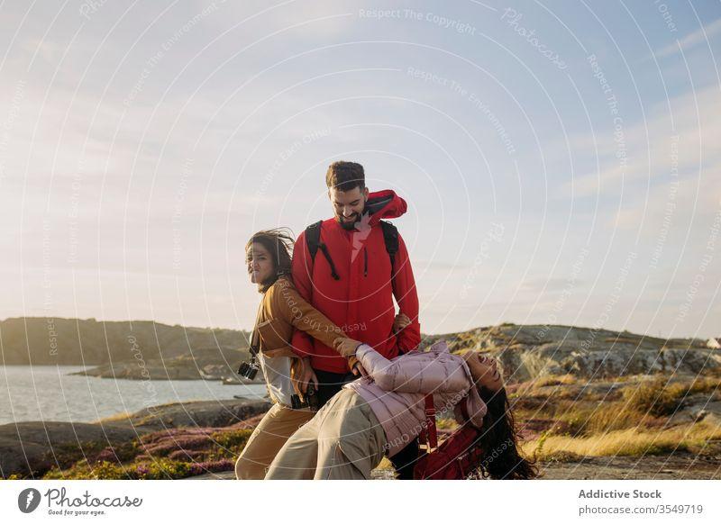 Gruppe positiver junger Touristen amüsiert sich am felsigen Meeresufer Menschengruppe Zusammensein heiter Spaß spielerisch Tourismus Oberbekleidung Natur Klippe