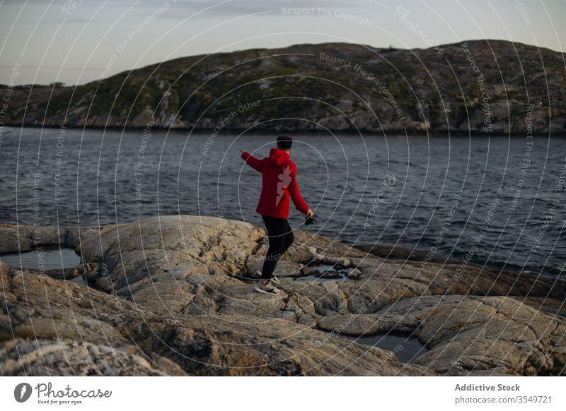 Männlicher Tourist mit Fotokamera am felsigen Seeufer stehend Mann Fotoapparat Felsen reisen nachdenken Hügel wolkig Himmel Fluss Stein erkunden Urlaub