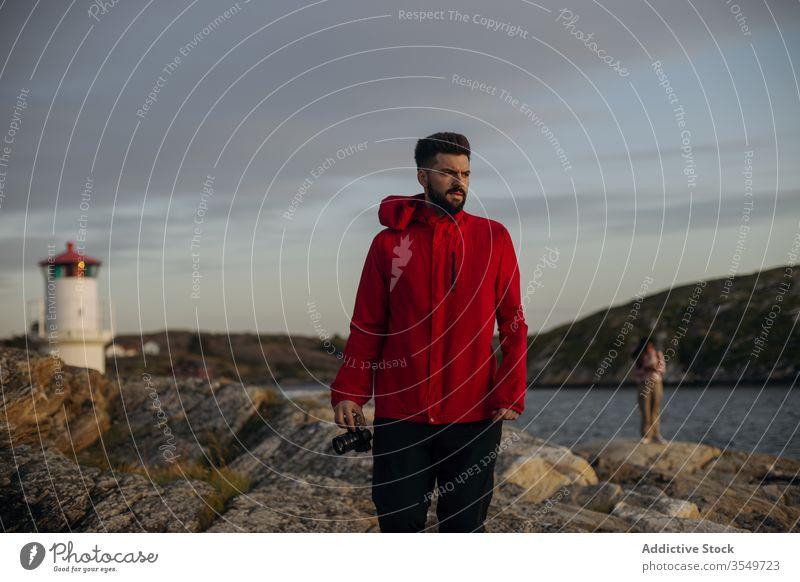 Männlicher Tourist mit Fotokamera am felsigen Seeufer stehend Fotoapparat Felsen Aussichtsturm reisen nachdenken Hügel wolkig Himmel Fluss Stein erkunden Urlaub