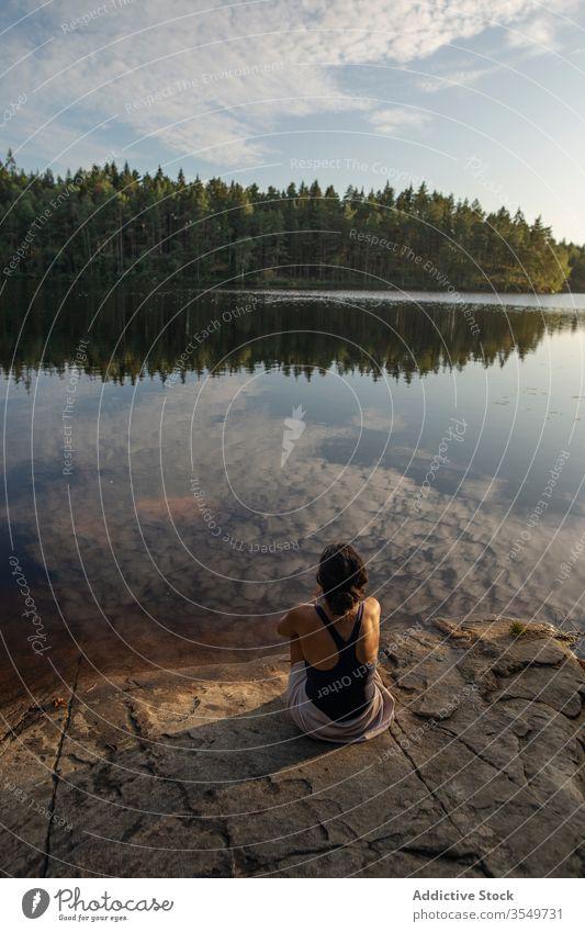 Frau im Badeanzug sitzt im Sommer am Seeufer Ufer genießen Landschaft felsig Küste Wald majestätisch ruhig Windstille Gelassenheit Harmonie friedlich idyllisch
