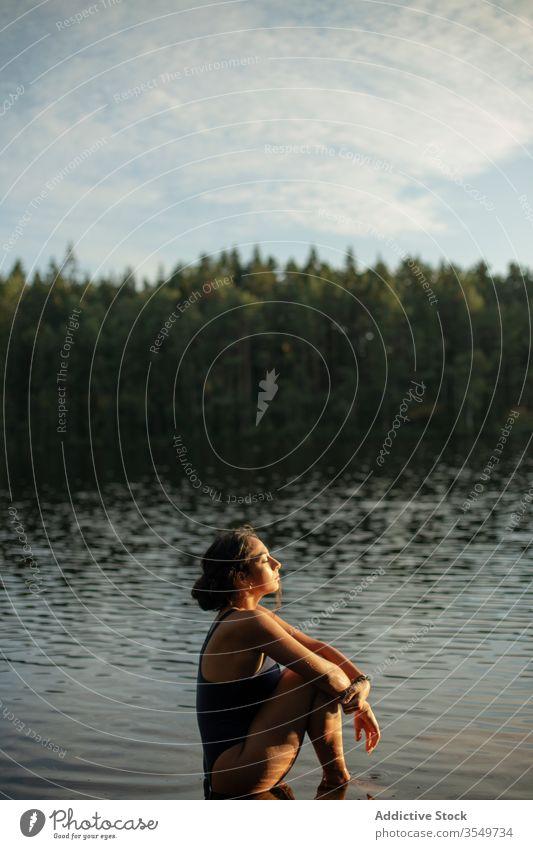 Frau im Badeanzug sitzt im See Wasser Windstille Sonnenuntergang genießen Sommer majestätisch sitzen Landschaft Wald ruhig Gelassenheit Harmonie friedlich