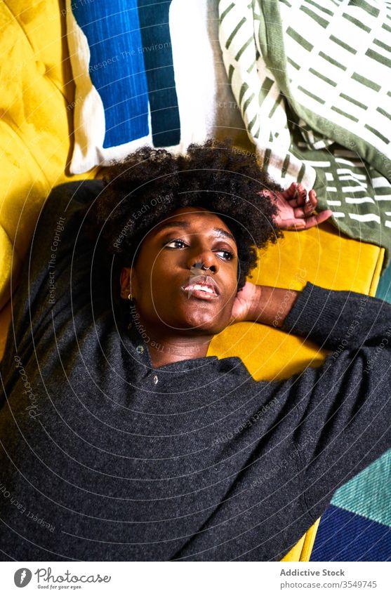 Junge schwarze Frau ruht auf farbenfrohem Sofa heimwärts Lügen gelangweilt besinnlich Design nachdenklich träumen jung Afroamerikaner lässig Liege ethnisch