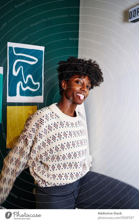Afroamerikanische Frau sitzt zu Hause auf der Couch heimwärts lässig Lächeln sitzen Afroamerikaner jung Zunge Aus heiter spielerisch ruhen Lifestyle schwarz