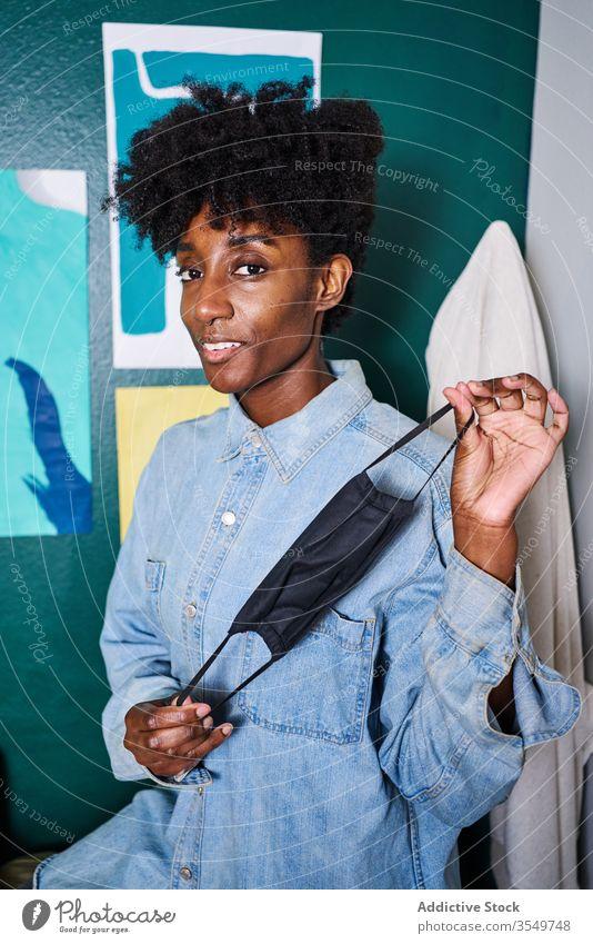 Junge schwarze Frau mit Schutzmaske in den Händen Mundschutz zu Hause bleiben Coronavirus COVID zeigen manifestieren behüten positiv jung Afroamerikaner